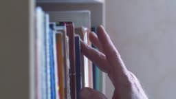 Man chooses a book on shelve. Dolly sliding shot along book stacks, moving from left to right. View of the various spine of books close up
