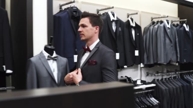 man choosing a suit at clothing store - abbigliamento video stock e b–roll