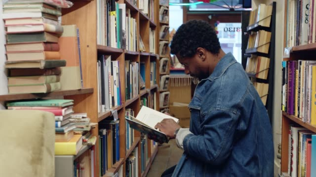 man choosing books in used bookstore - bookstore stock videos & royalty-free footage