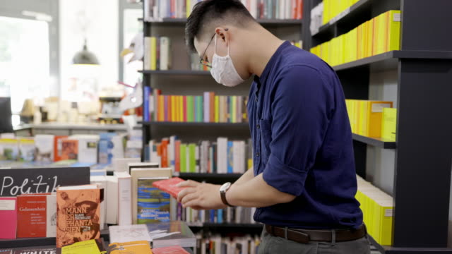 man choosing books to buy at bookstore - book shop stock videos & royalty-free footage