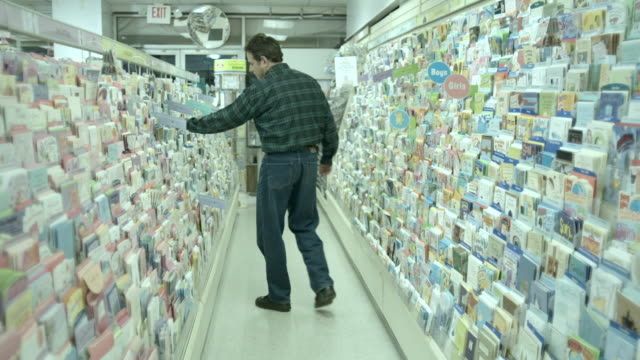 WS, FOCUSING, Man choosing greeting card in pharmacy aisle, Scotch Plains, New Jersey, USA