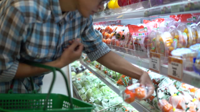 mann, die auswahl von produkten im supermarkt - lebensmittelhändler stock-videos und b-roll-filmmaterial
