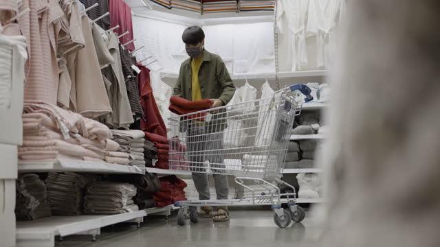 mann wählt das handtuch in einkaufszentrum - casual clothing stock-videos und b-roll-filmmaterial