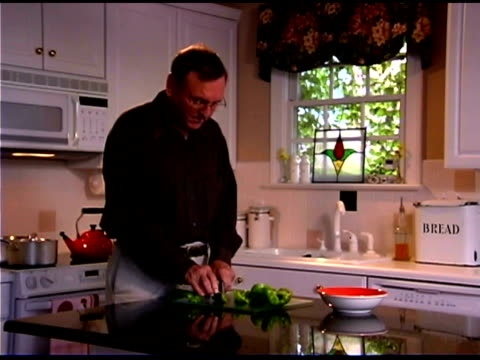 man chopping bell peppers in kitchen - dreiviertelansicht stock-videos und b-roll-filmmaterial