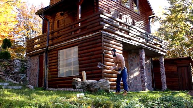 vídeos de stock, filmes e b-roll de homem cortando lenha na montanha - treehouse