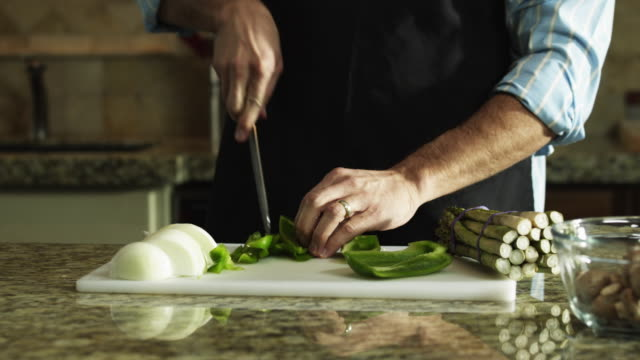 CU Man chopping green bell pepper, mid section / Orem, Utah, USA