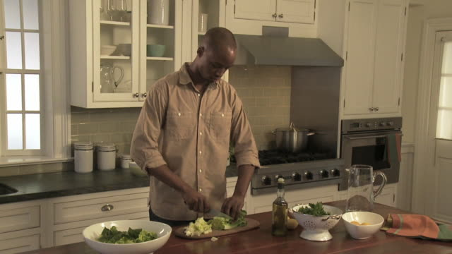 MS DS Man chopping lettuce and mixing salad in bowl / New York City, New York, USA