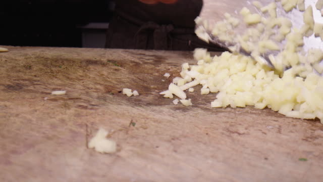 man chopping onion using cleaver on woode cutting board - chopping stock videos & royalty-free footage