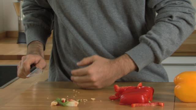 Man chopping peppers; UK