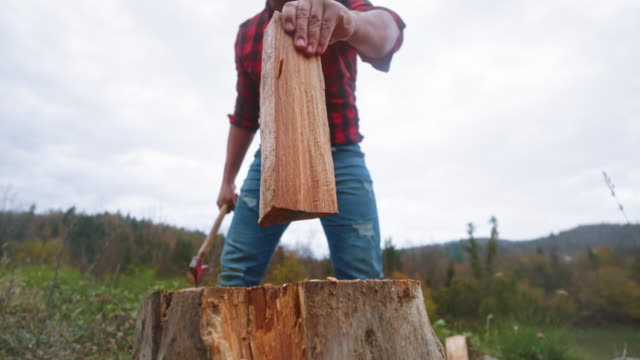 slo mo man chopping wood with his axe outside - tartan stock videos & royalty-free footage
