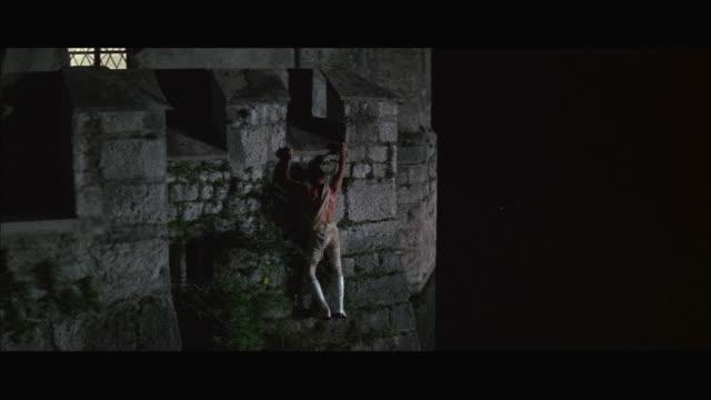 ms tu man clambering fortress wall at night - schlossgebäude stock-videos und b-roll-filmmaterial