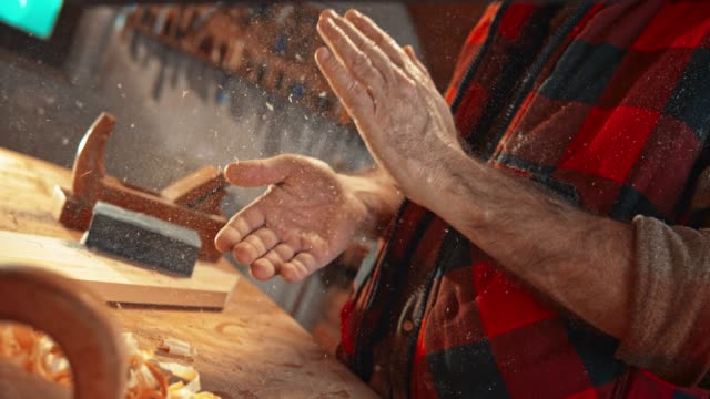 slo mo ld man clapping hands in the workshop to get wood dust off his hands - work tool stock videos & royalty-free footage