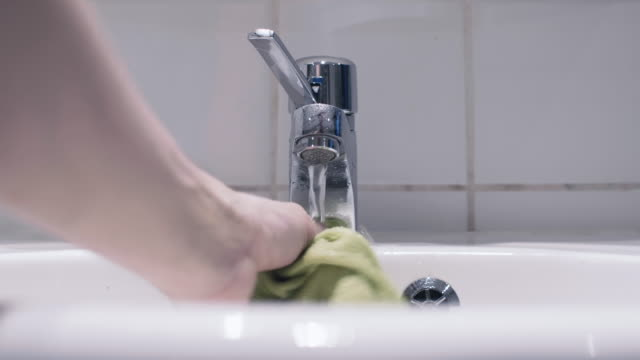man cleaning a bathroom sink and faucet - towel stock videos & royalty-free footage