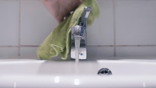 Man Cleaning a Bathroom Sink and Faucet