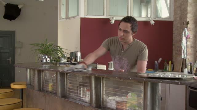 la ms tu man cleaning counter in modern kitchen / berlin, germany - ぞうきん点の映像素材/bロール