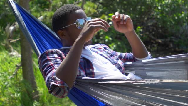 a man cleaning his sunglasses while resting in a hammock near a mountain lake. - プレイドシャツ点の映像素材/bロール