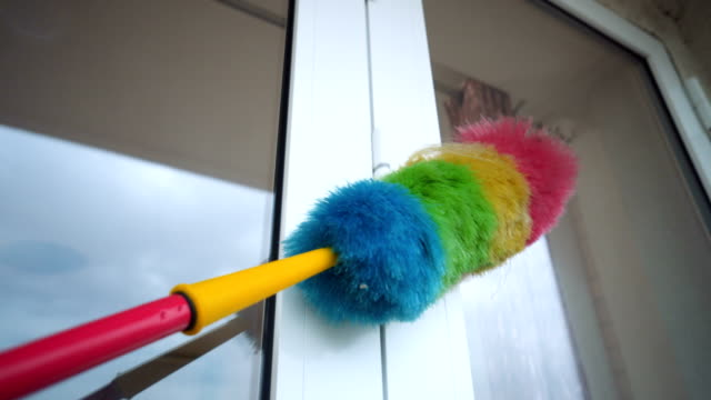 Man cleaning home with duster