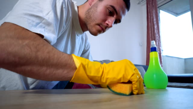 Man cleaning home with protective gloves