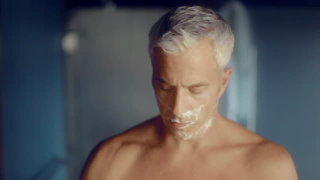 MS Man cleaning shaving cream with towel in hotel room  / Seattle, WA, United States