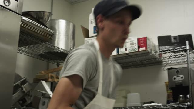 ms shaky man cleaning steel counter in commercial kitchen, salt lake city, utah, usa - ステンレス点の映像素材/bロール