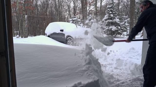 vídeos de stock, filmes e b-roll de homem limpando a saída da garagem para a calçada coberta de neve depois de uma tempestade de neve de inverno, usando a pá. - digging