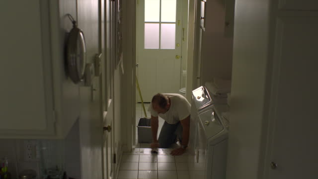 WS, Man cleaning tile floor in laundry room, Hollywood, California, USA
