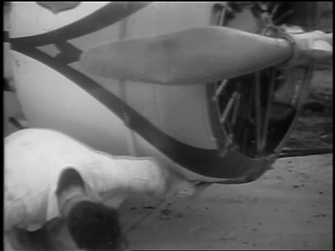 vidéos et rushes de b/w 1935 man cleaning underside of winnie mae prop plane on airfield / cleveland oh / newsreel - 1935