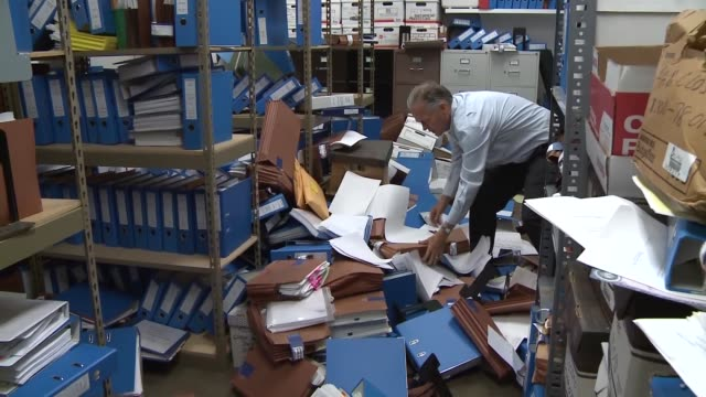 man cleans up binders papers strewn on floor following napa california 60 earthquake - napa california video stock e b–roll