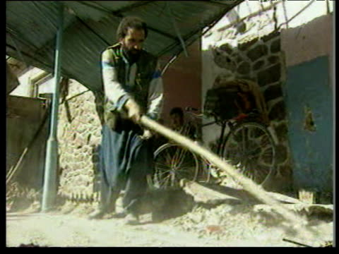 Man clearing away debris with spade following bombing raids during Afghan Civil War between pro government and Taliban forces Kabul Oct 96