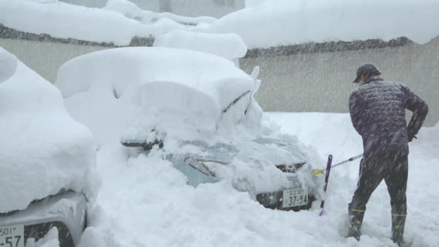 man clears car of thick snow after major winter storm hits northern japan - 濃い点の映像素材/bロール