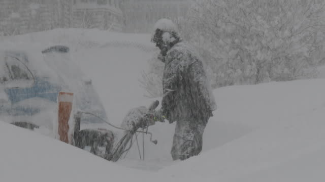 a man clears his driveway with a snowblower in adams new york during a lake effect storm that dumped over 5 feet of snow on the area - scott mcpartland stock videos & royalty-free footage