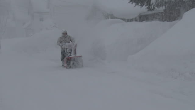 a man clears his walkway with a snowblower in adams new york during a lake effect storm that dumped over 5 feet of snow on the area - scott mcpartland stock videos and b-roll footage