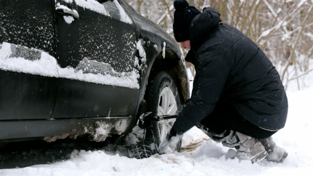 man clears snow near the wheel of a car. - spade stock videos & royalty-free footage