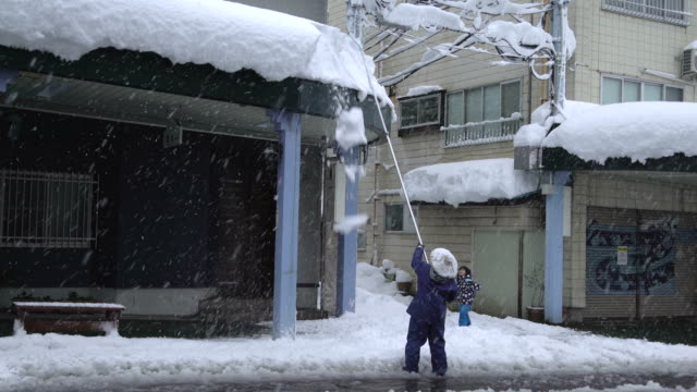 Man clears thick overhanging snow from side walk roof top as major winter storm hits Japan