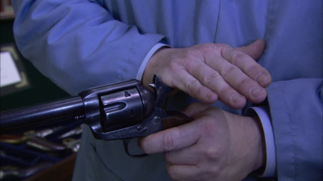 a man clicks the hammer of a handgun with the side of his hand to turn an empty revolver. - präsentation hinter glas stock-videos und b-roll-filmmaterial