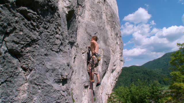 hd crane: man climbing a rock - rock climbing stock videos and b-roll footage