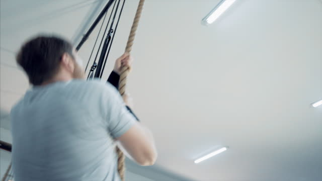 Man climbing a rope.