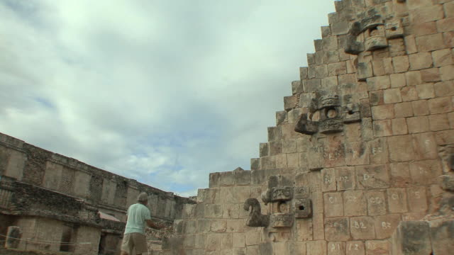 WS Man climbing Adivino (Pyramid of Magician) at pre-Columbian ruined city of Maya civilization / Uxmal, Yucatan, Mexico