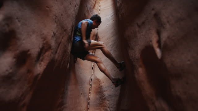 ws la man climbing canyon / lake powell, utah, usa - スロット渓谷点の映像素材/bロール