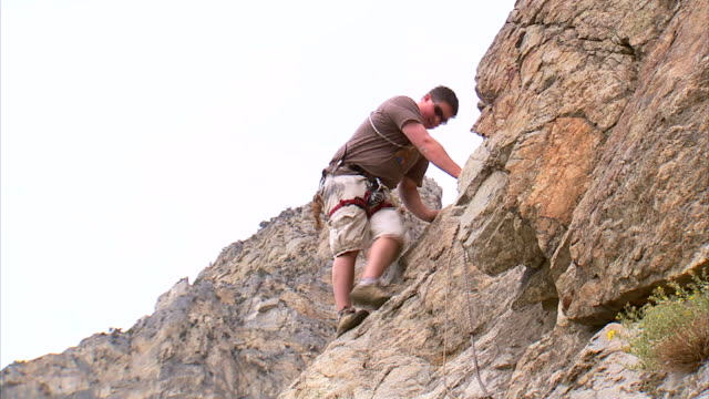 vídeos de stock e filmes b-roll de ws la man climbing down face of mountain / provo, utah, usa - provo