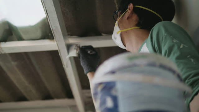 man climbing ladder and painting inside room. - house painter stock videos and b-roll footage