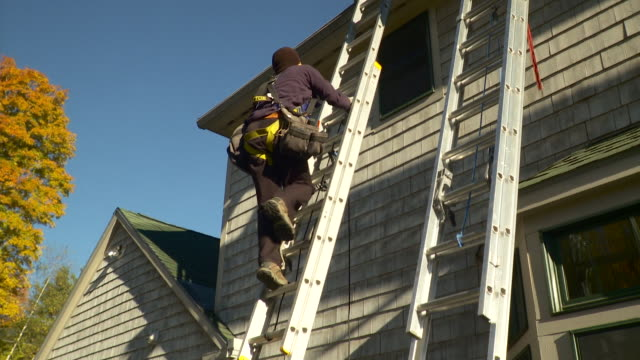 vidéos et rushes de ws tu man climbing ladder to roof while carrying wire / greenfield, massachusetts, usa - un seul homme d'âge moyen