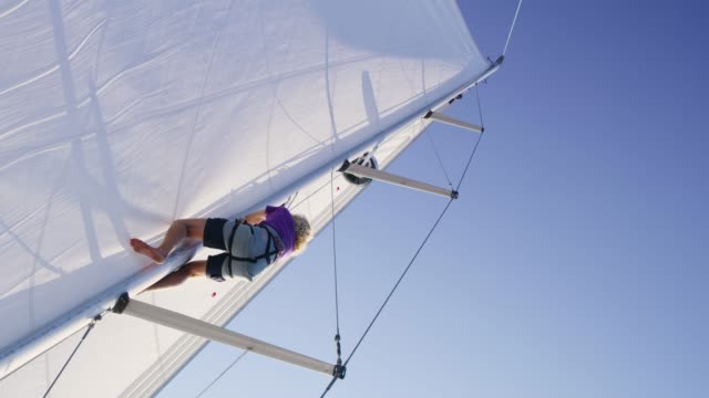 man climbing mast on sunny sailboat, real time - sailing stock videos & royalty-free footage