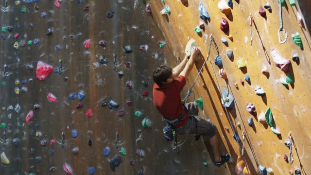 man climbing on an indoor climbing wall - kletterwand kletterausrüstung stock-videos und b-roll-filmmaterial