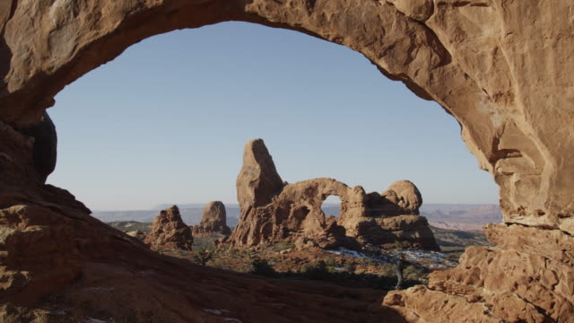 WS Man climbing on arch rock formation / Arches National Park, Moab, Utah, USA