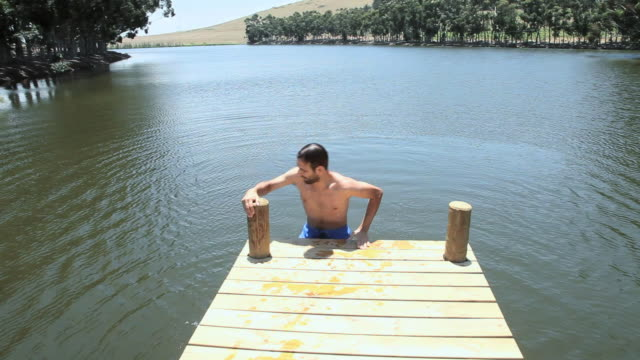Man climbing out of lake onto jetty