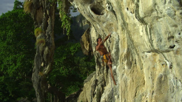 ms man climbing rock face with bare feet, clipping rope into karabiner, dipping hand in chalk-bag and ascending / krabi, thailand - hex climbing equipment stock videos and b-roll footage