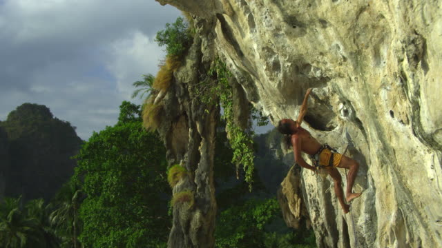 ms man climbing rock face with bare feet, clipping rope into karabiner, dipping hand in chalk-bag / krabi, thailand - hex climbing equipment stock videos and b-roll footage