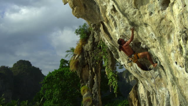 ms man climbing rock face with bare feet, dipping hand in chalk-bag, clipping rope into karabiner / krabi, thailand - hex climbing equipment stock videos and b-roll footage
