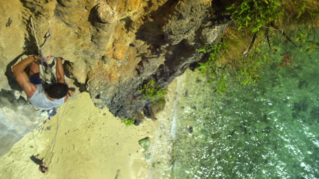 ms man climbing rock facerock face, beach and sea in background, woman belaying below, man dipping hand into chalk-bag, looking up and ascending / krabi, thailand - rock face stock videos & royalty-free footage